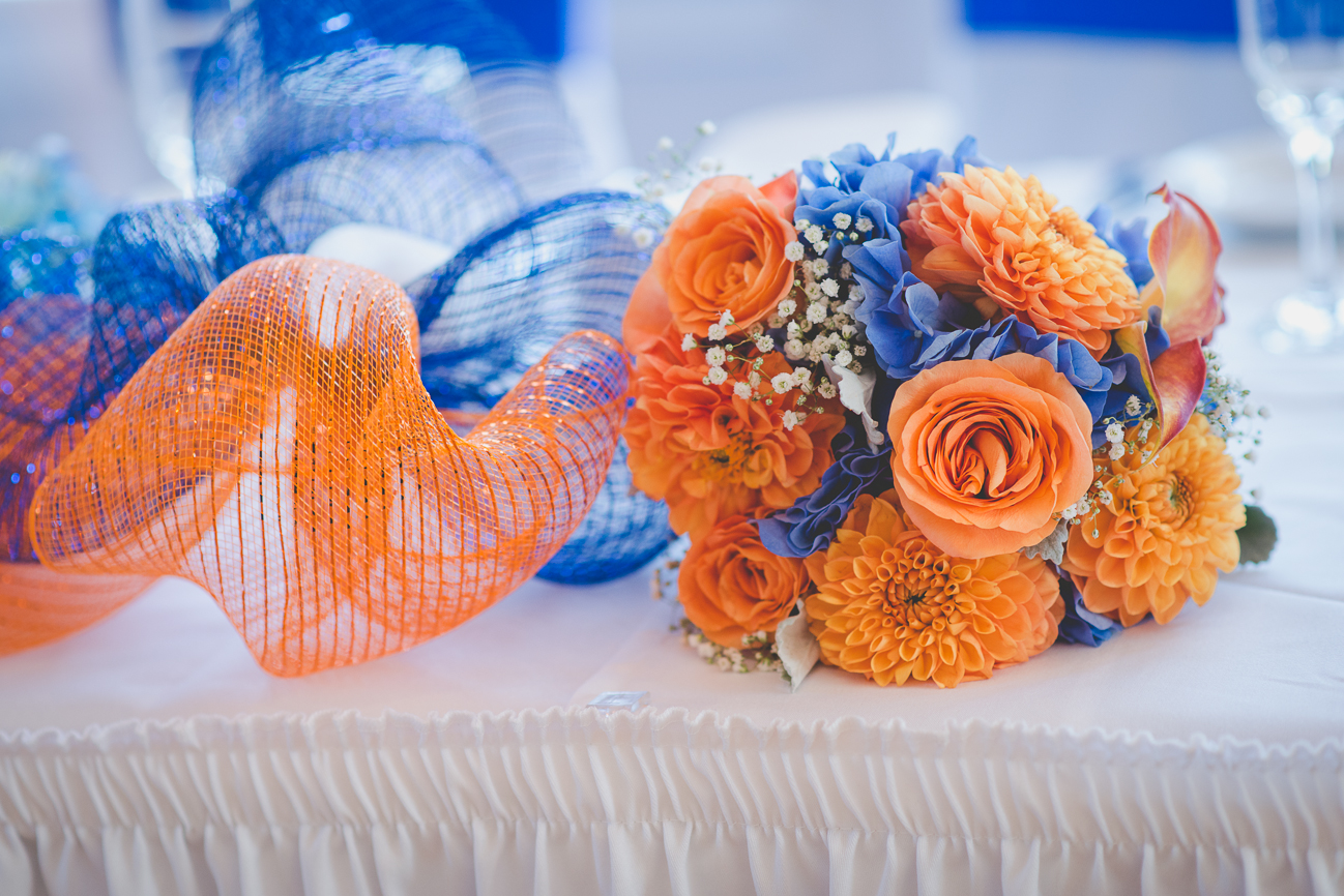 orange and blue rose, dahlia, and baby's breath bridal bouquet