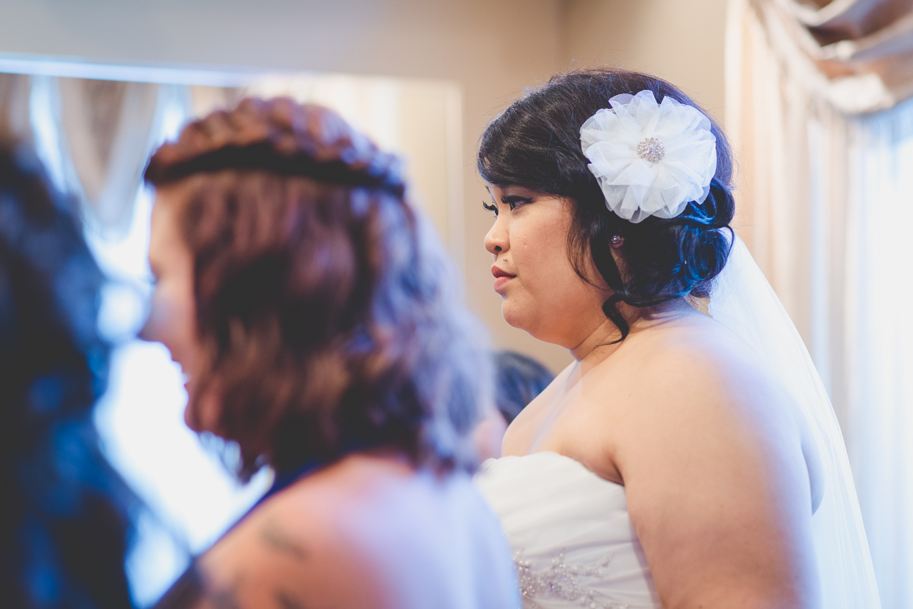 bride with white hair flower, monroe piercing, and veil waiting for wedding ceremony