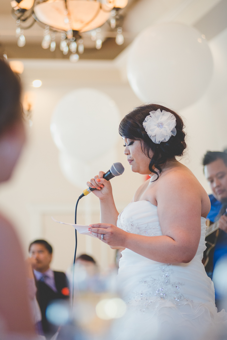 bride in ruffled sweetheart wedding dress and hair flower surprises groom with a song at wedding reception