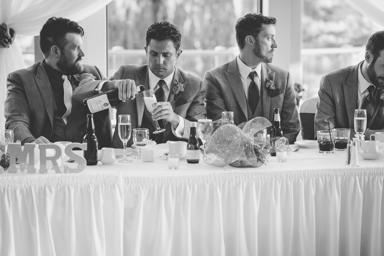 best man pouring champagne during toasts at wedding reception