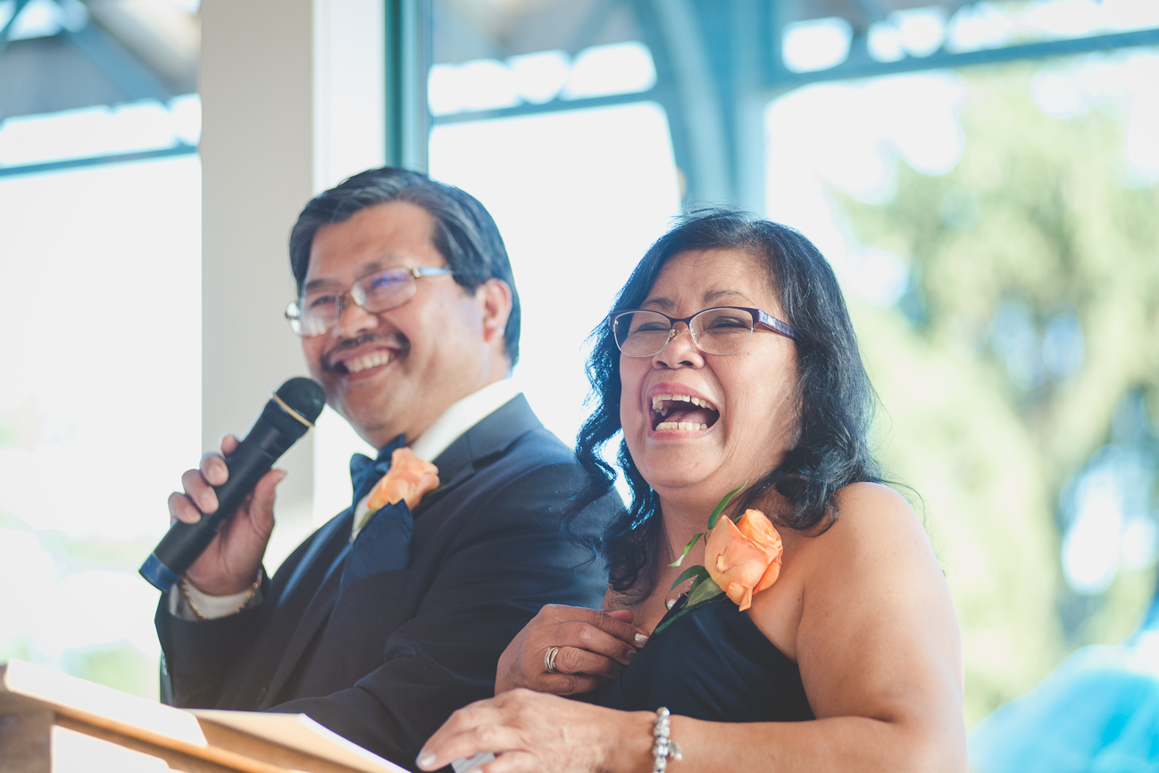 mother of the bride and father of the bride laughing during toast at wedding reception