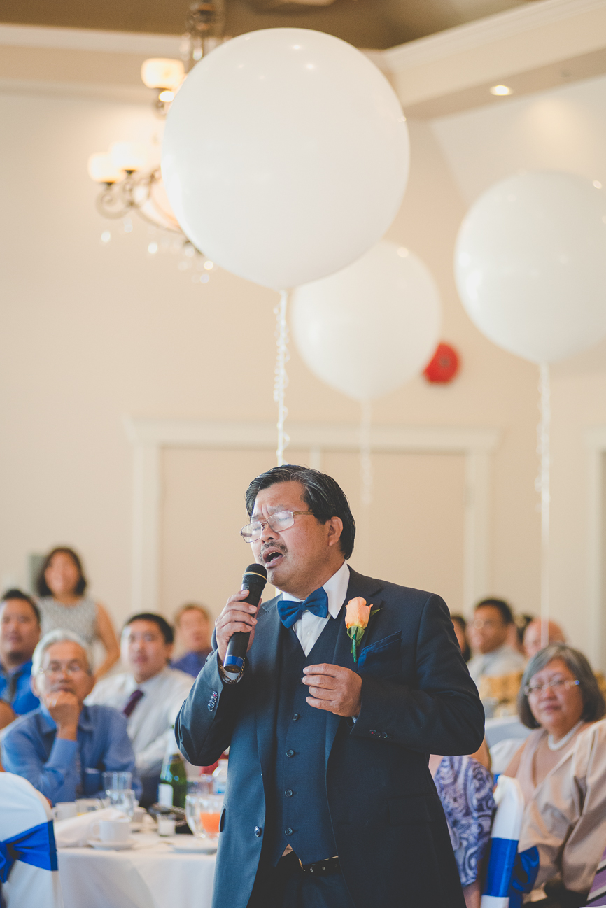 father of the bride sings Can't Help Falling in Love With You during toasts at wedding reception with giant white balloons