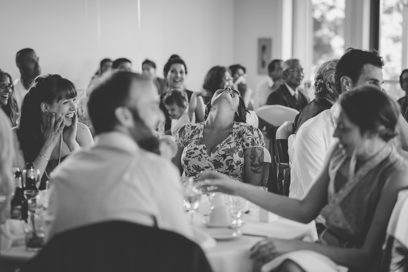 guests laughing during toasts at wedding reception
