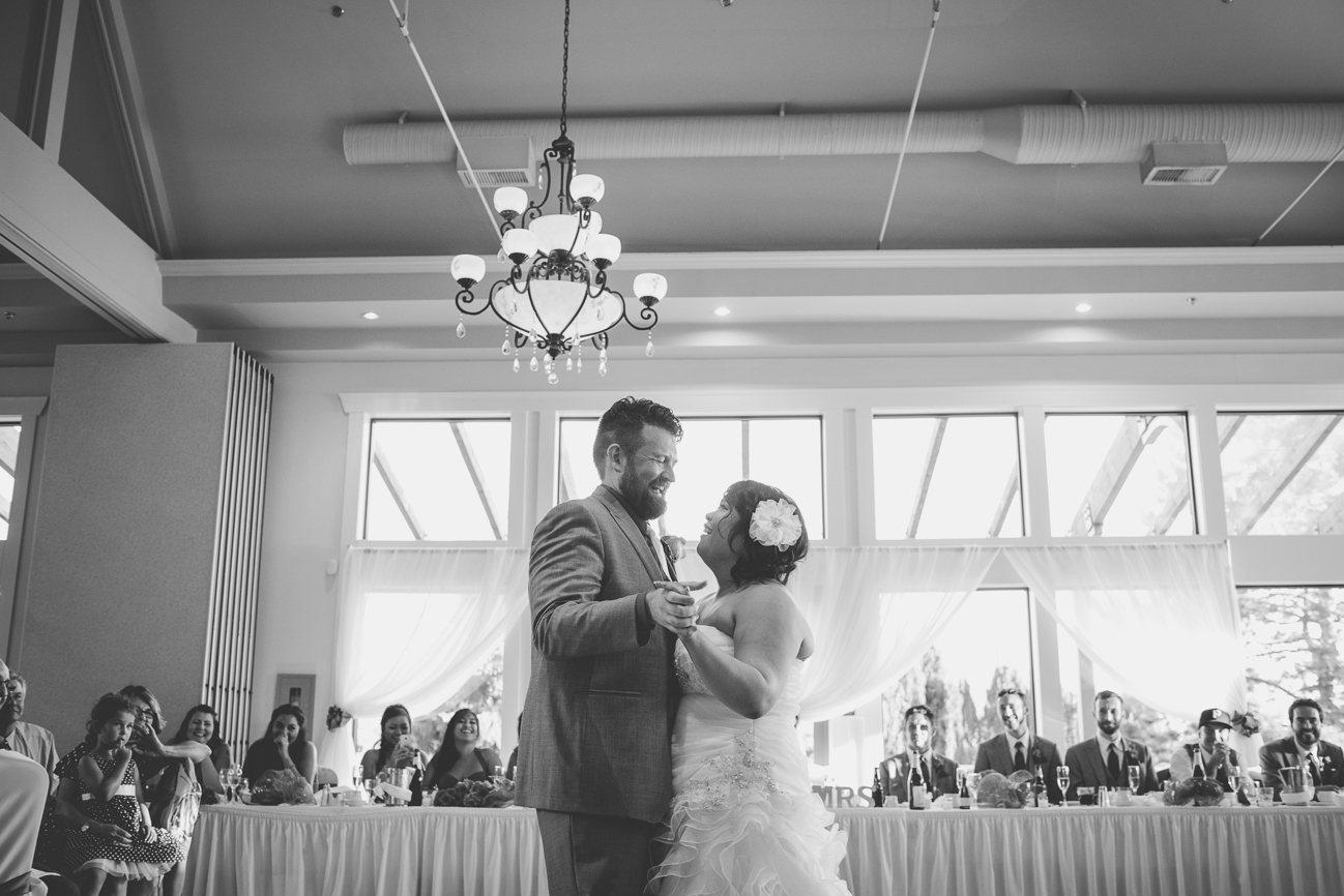 groom in grey suit with cobalt blue shirt and white tie and bride in sweetheart neckline wedding dress with hair flower dance in front of head table during first dance at wedding reception