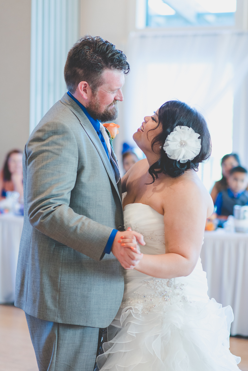 groom in grey suit with cobalt blue shirt and white tie and bride in sweetheart neckline wedding dress with hair flower dance during first dance at wedding reception