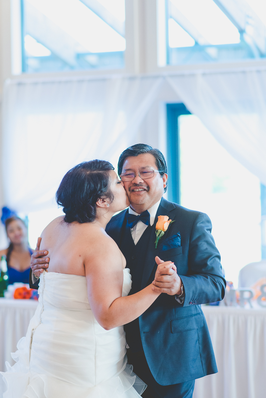 bride kisses father on cheek during father daughter dance at wedding reception