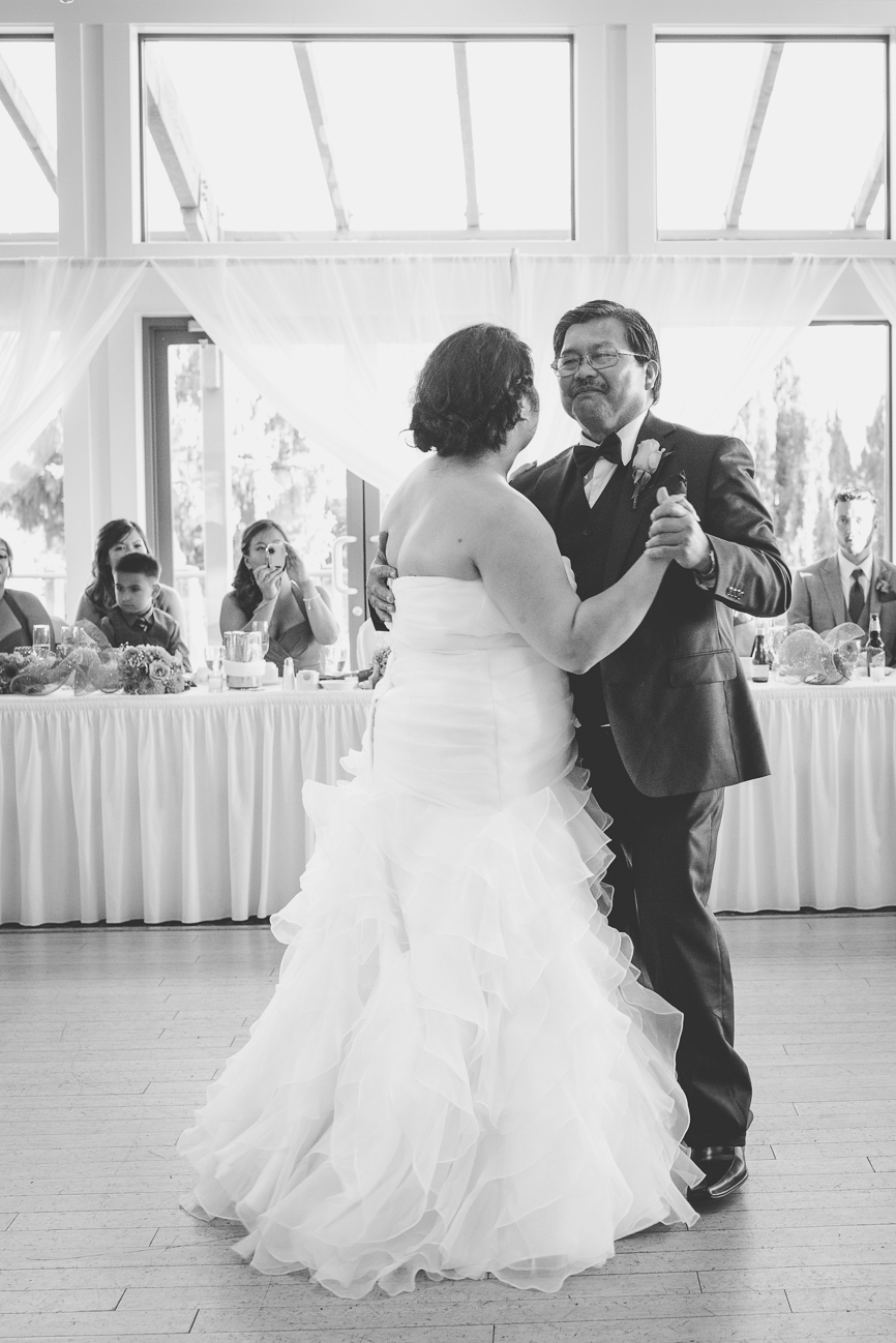 bride dances with father during father daughter dance at golf course wedding reception