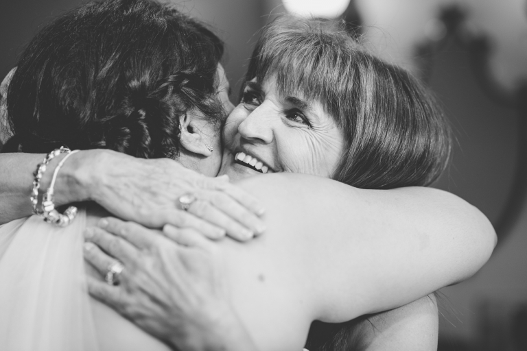 mother of the groom hugging bride before wedding ceremony