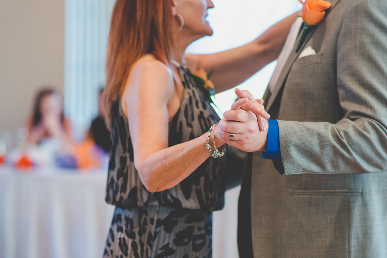 close up of groom's wedding band during mother son dance at wedding reception