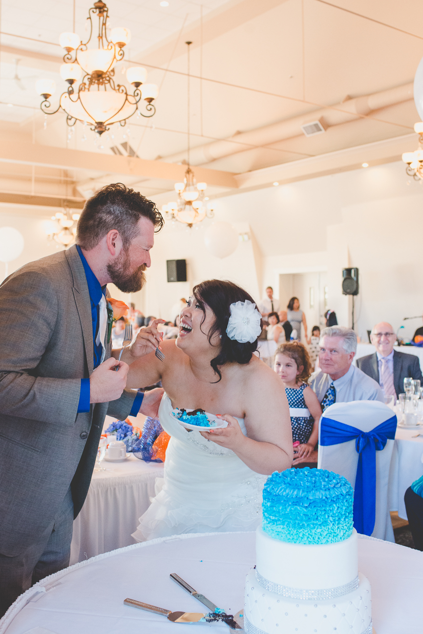 groom in grey suit with cobalt blue shirt and white tie and bride in sweetheart neckline wedding dress with turquoise ruffled wedding cake during cake cutting
