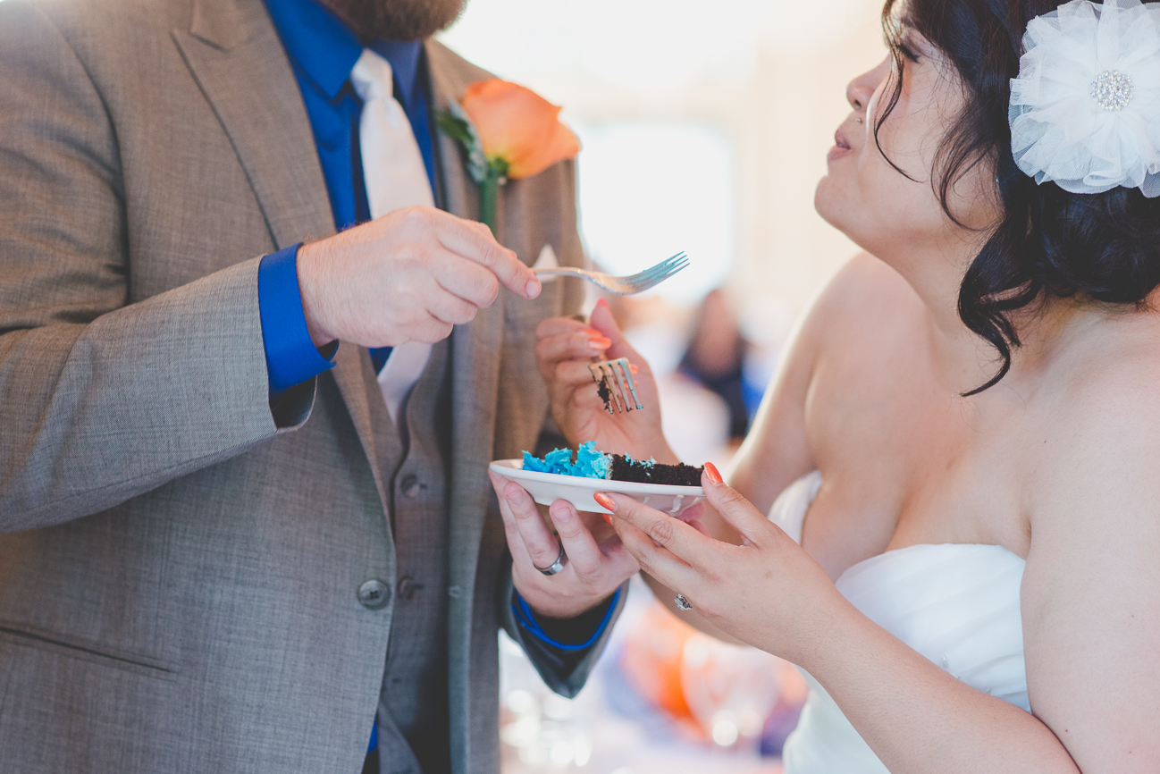 groom in grey suit with cobalt blue shirt and white tie and bride in sweetheart neckline wedding dress with hair flower eat turquoise ruffled wedding cake during cake cutting