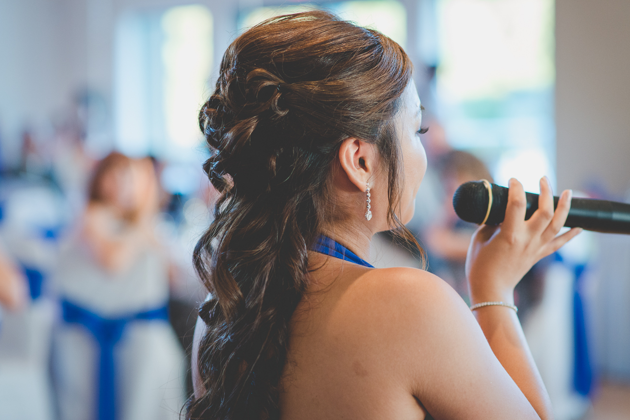 bridesmaid in cobalt blue dress sings to bride and groom during wedding reception