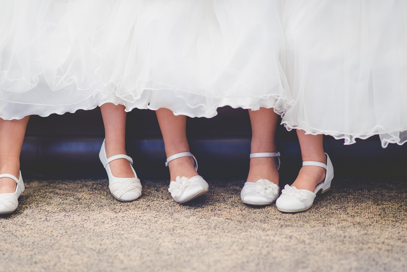 three flower girls feet in white shoes before wedding ceremony