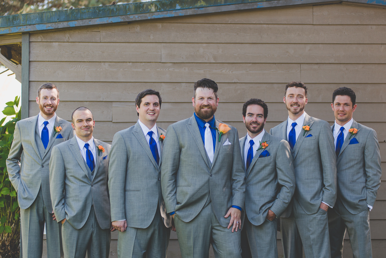 groomsmen in grey suits with cobalt blue ties and orange rose boutonnieres