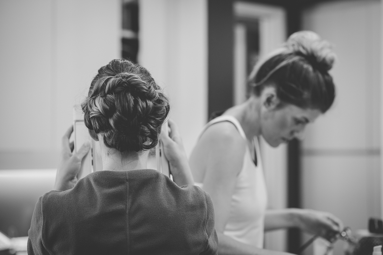 bride looking at hair and make-up in mirror while getting ready for wedding day