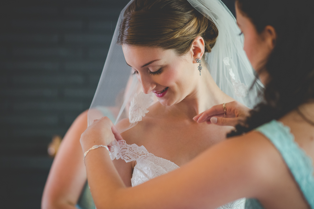 bridesmaids helping bride with her lace wedding dress and veil before wedding ceremony