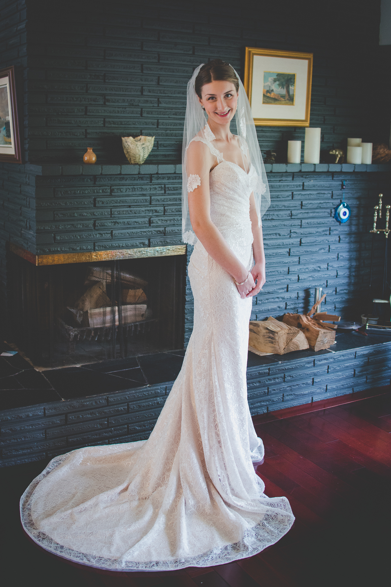 bride in latte lace wedding dress and veil standing by her parent's fire place