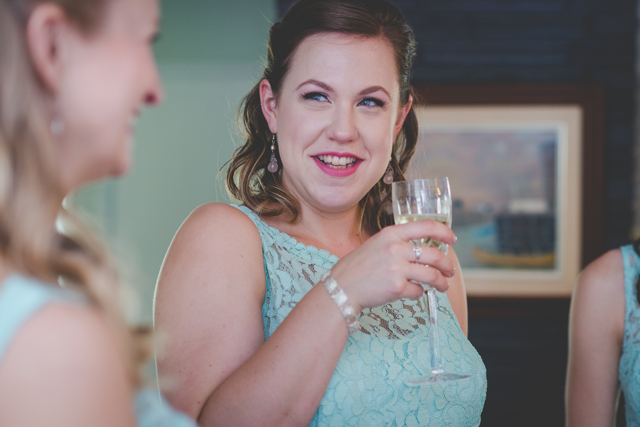 bridesmaid in turquoise dress laughing and drinking champagne before wedding ceremony