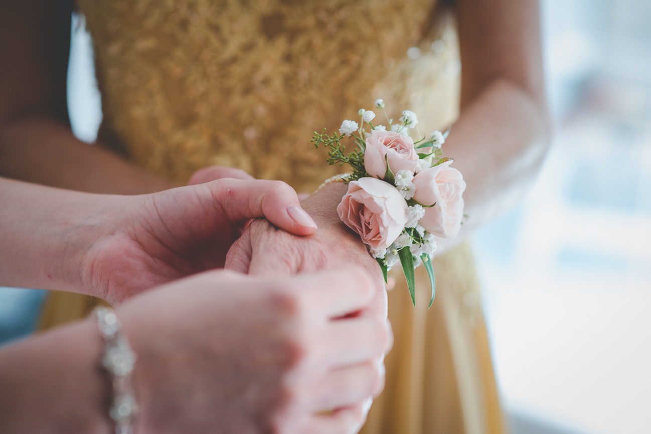 mother of the bride in yellow dress putting on her wrist corsage before wedding ceremony