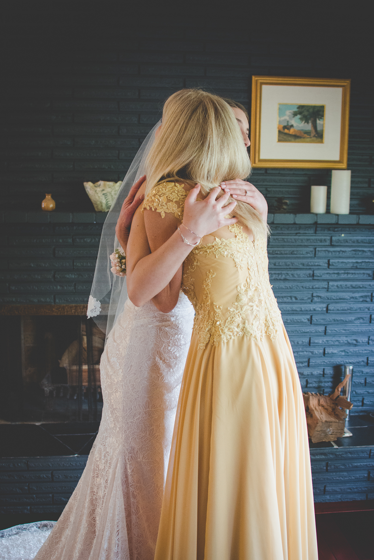 bride hugging mother of the bride in yellow dress before wedding ceremony