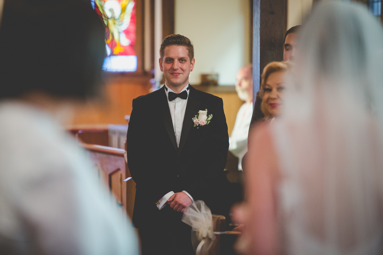 groom standing at the altar sees his bride for the first time as she comes down the aisle with her father