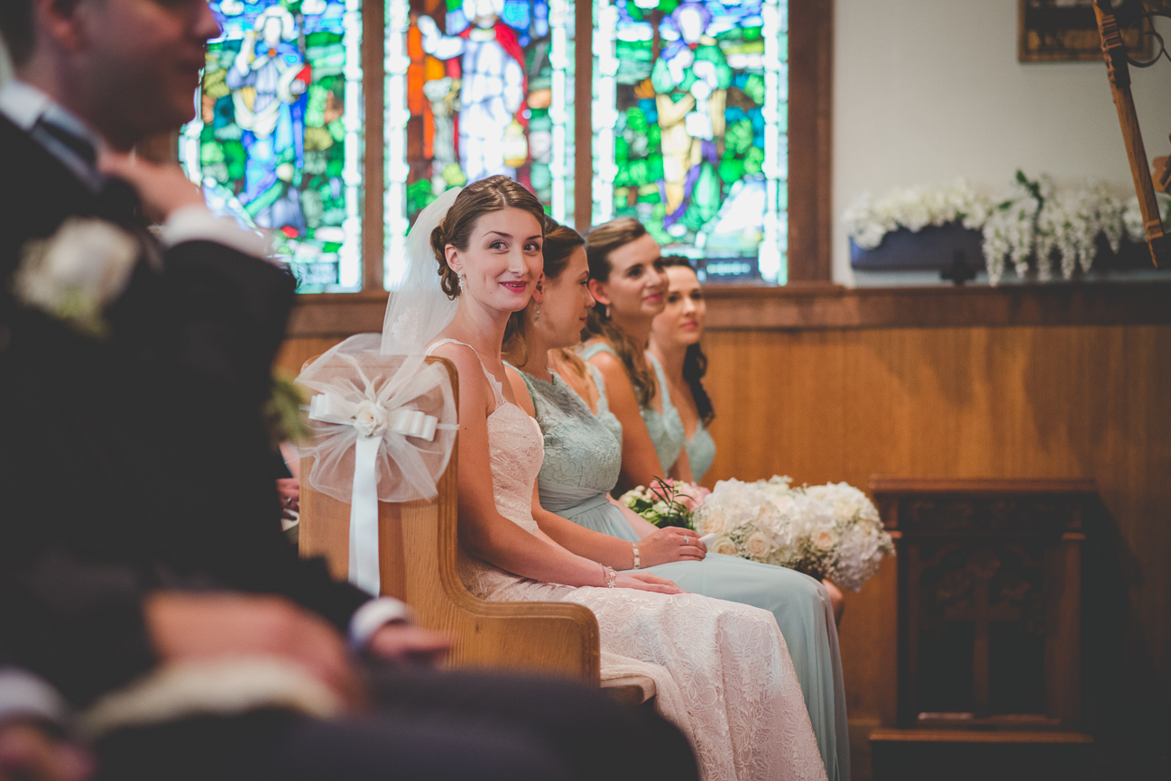 bride smiling at groom from another pew during church wedding ceremony