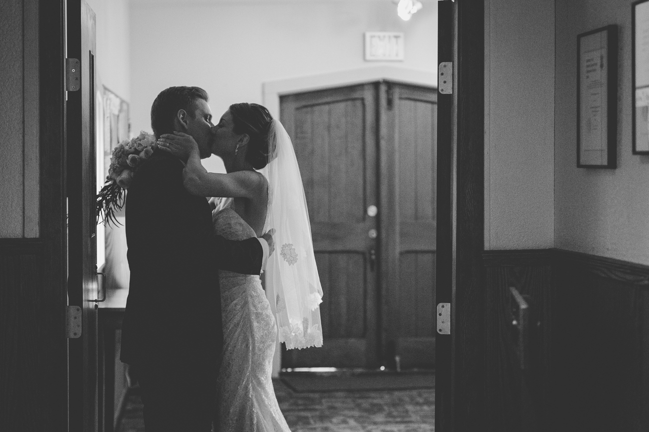 bride and groom sneak a kiss at the end of the aisle after being announced husband and wife