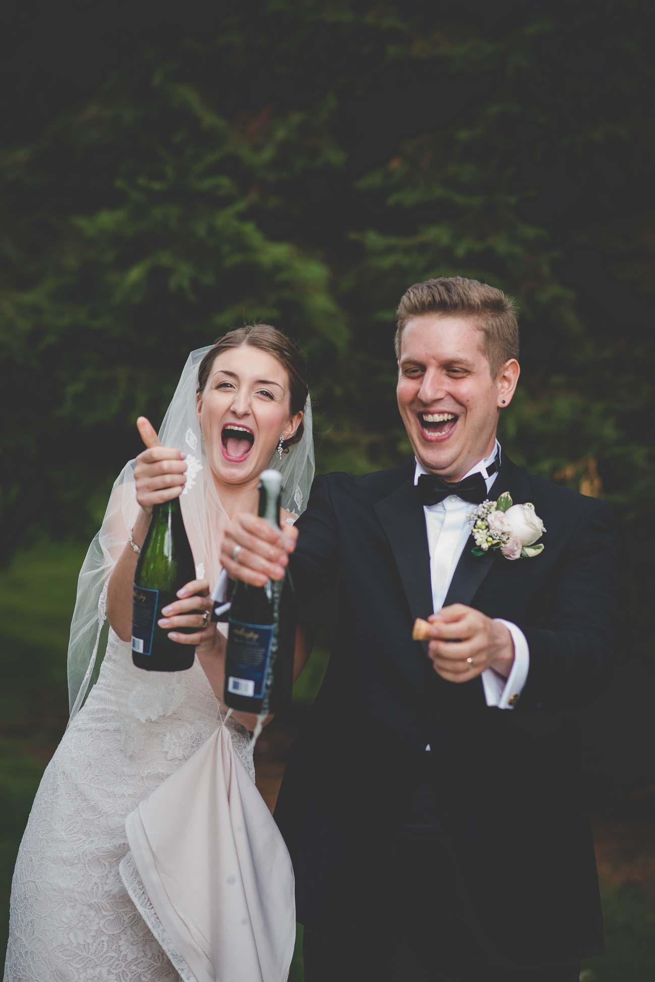 bride and groom popping champagne bottles with wedding party after wedding ceremony