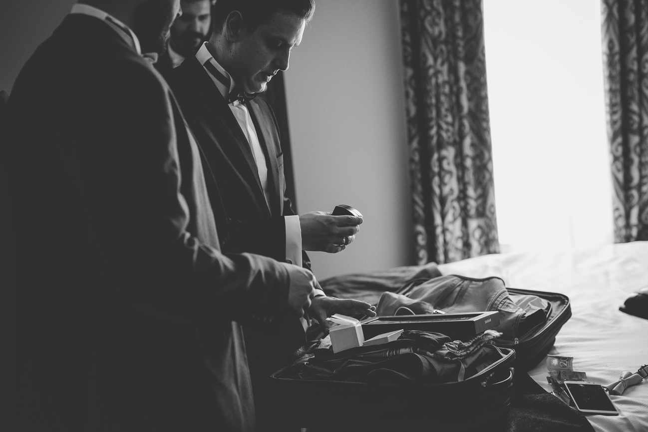 groom looking at wedding ring box before wedding ceremony