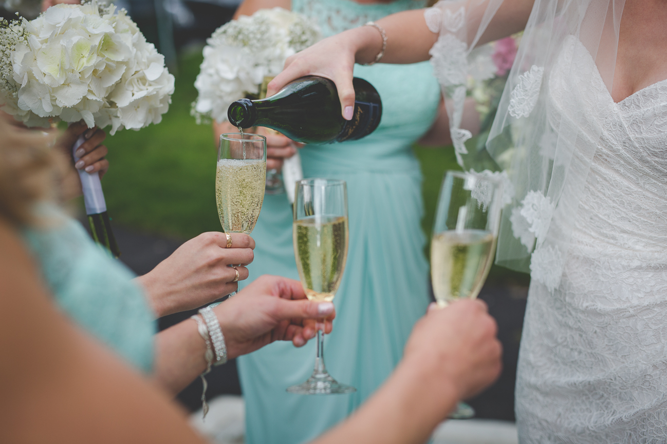 bride pours champagne for bridesmaids to toast after church wedding ceremony