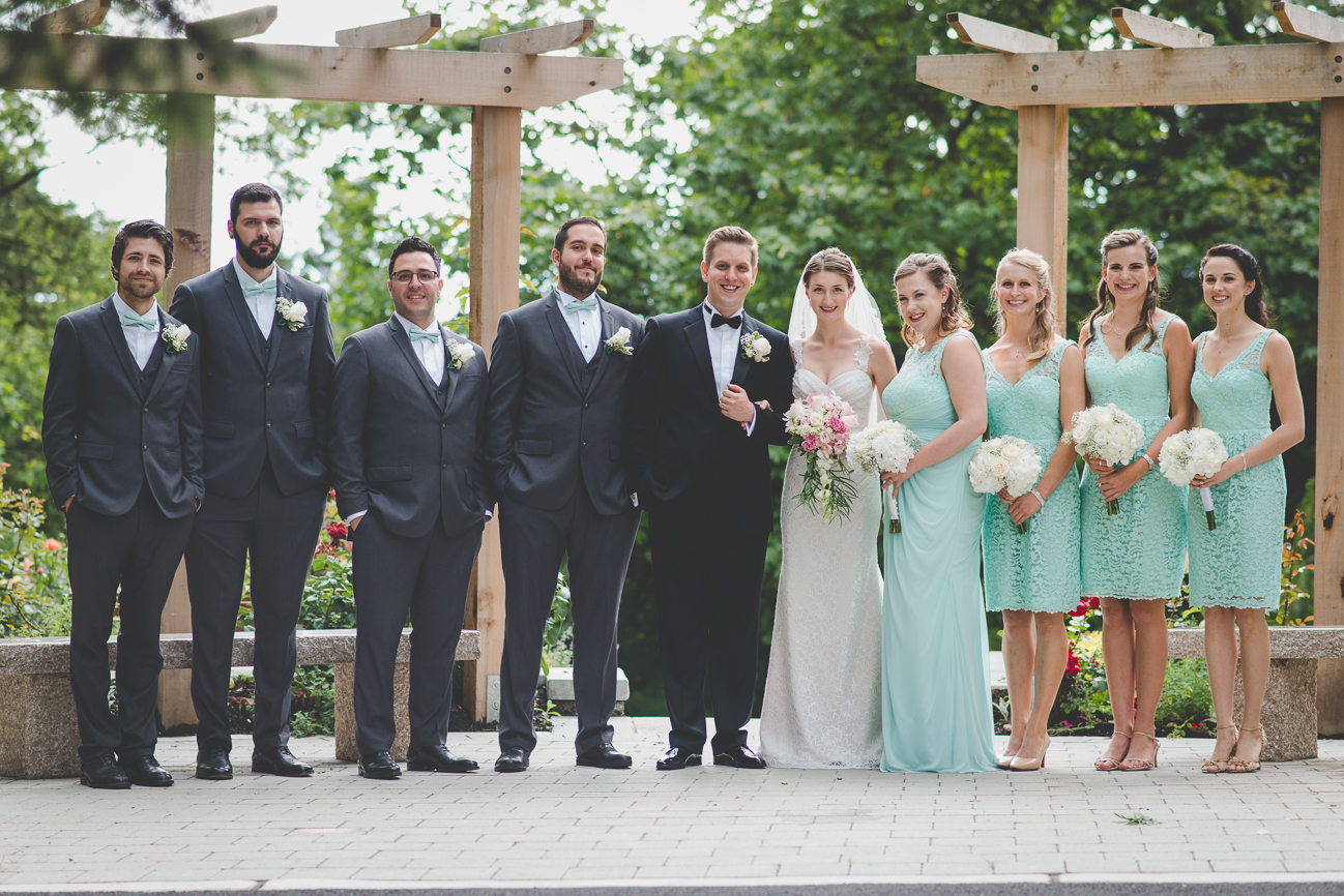 bride in lace wedding dress and groom in black tux and bow tie with bridesmaids in lace turquoise dresses and groomsmen in gray suits with turquoise bow ties