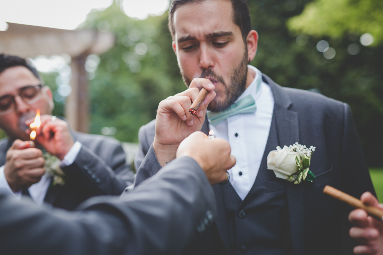 best man smoking a cigar after church wedding ceremony