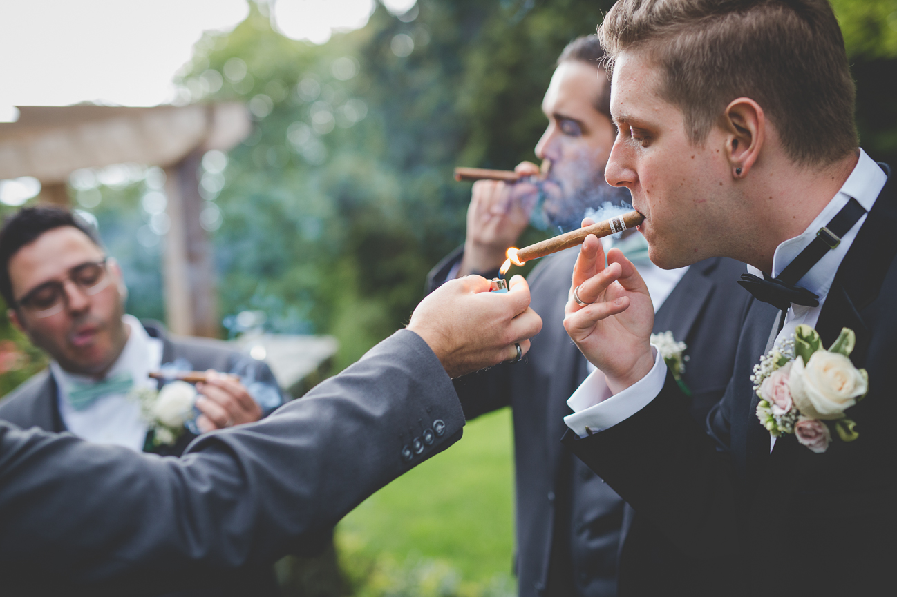 groom lighting a cigar with groomsmen after church wedding ceremony
