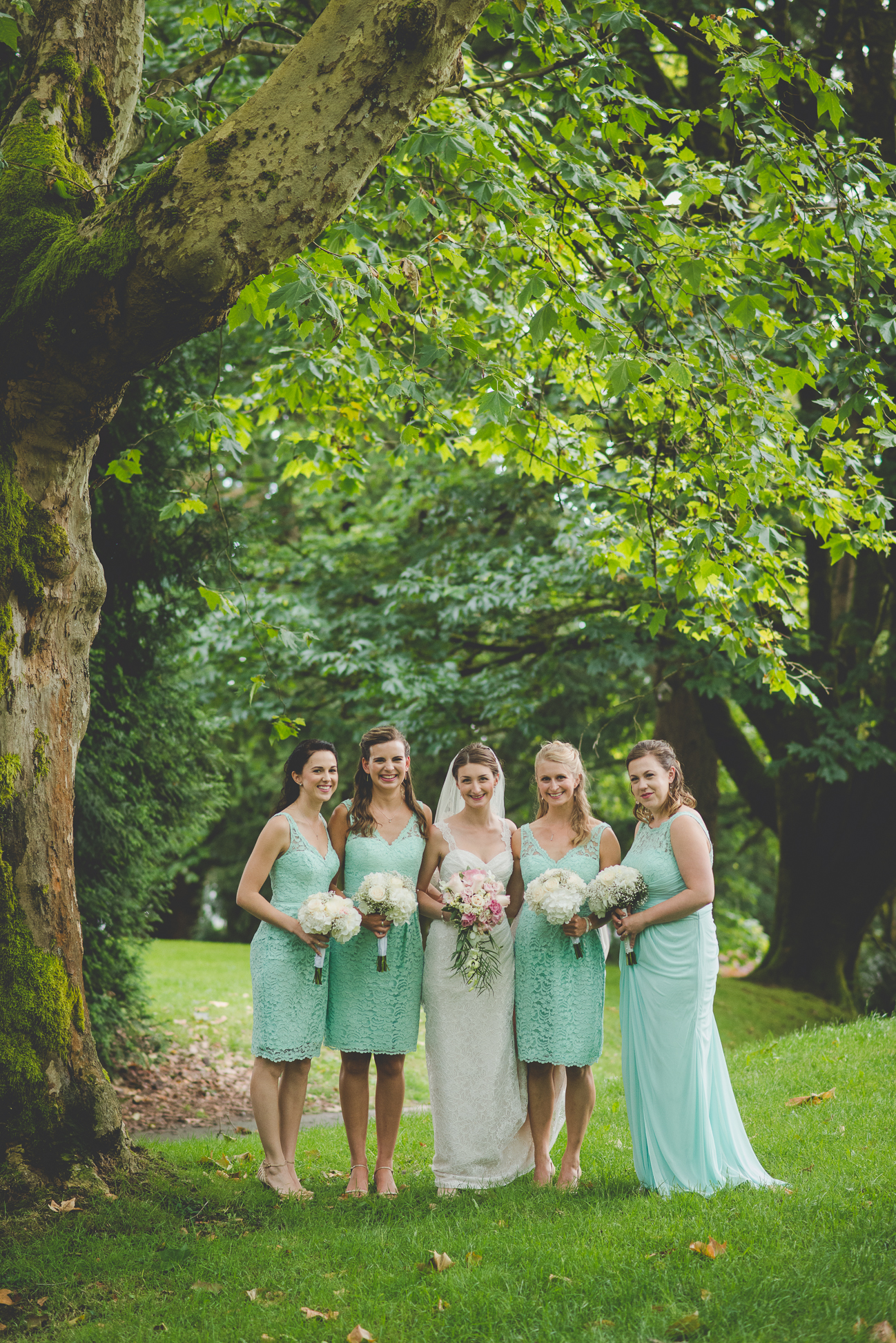 bride in latte lace dress with cascading bouquet with bridesmaids in short lace turquoise dresses and white bouquets
