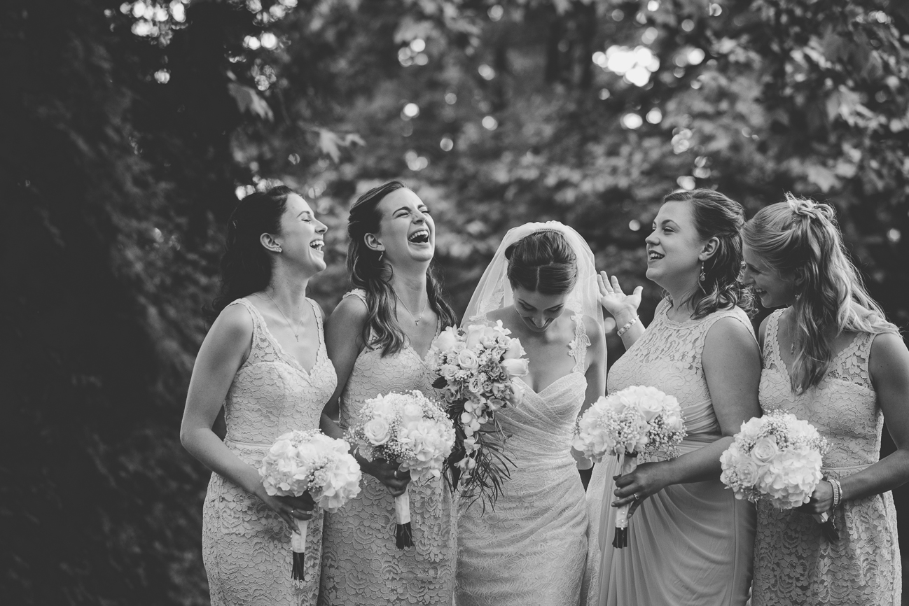 bride and bridesmaids laughing after wedding ceremony