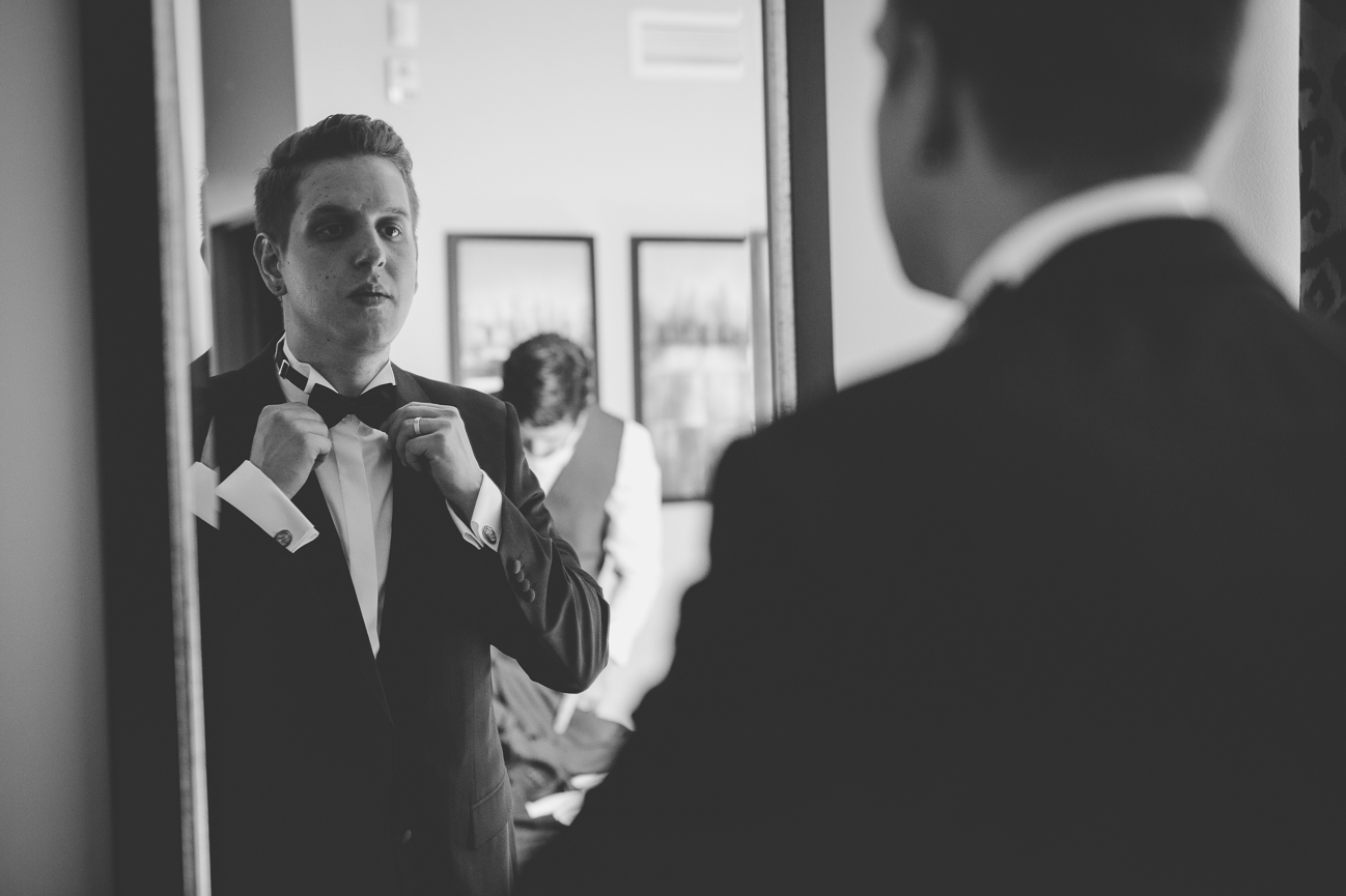 groom fixing his bow tie in the mirror before wedding ceremony