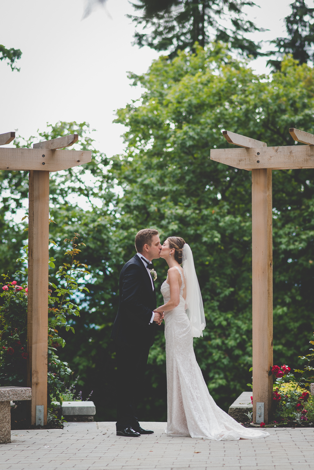bride and groom kiss in rose garden