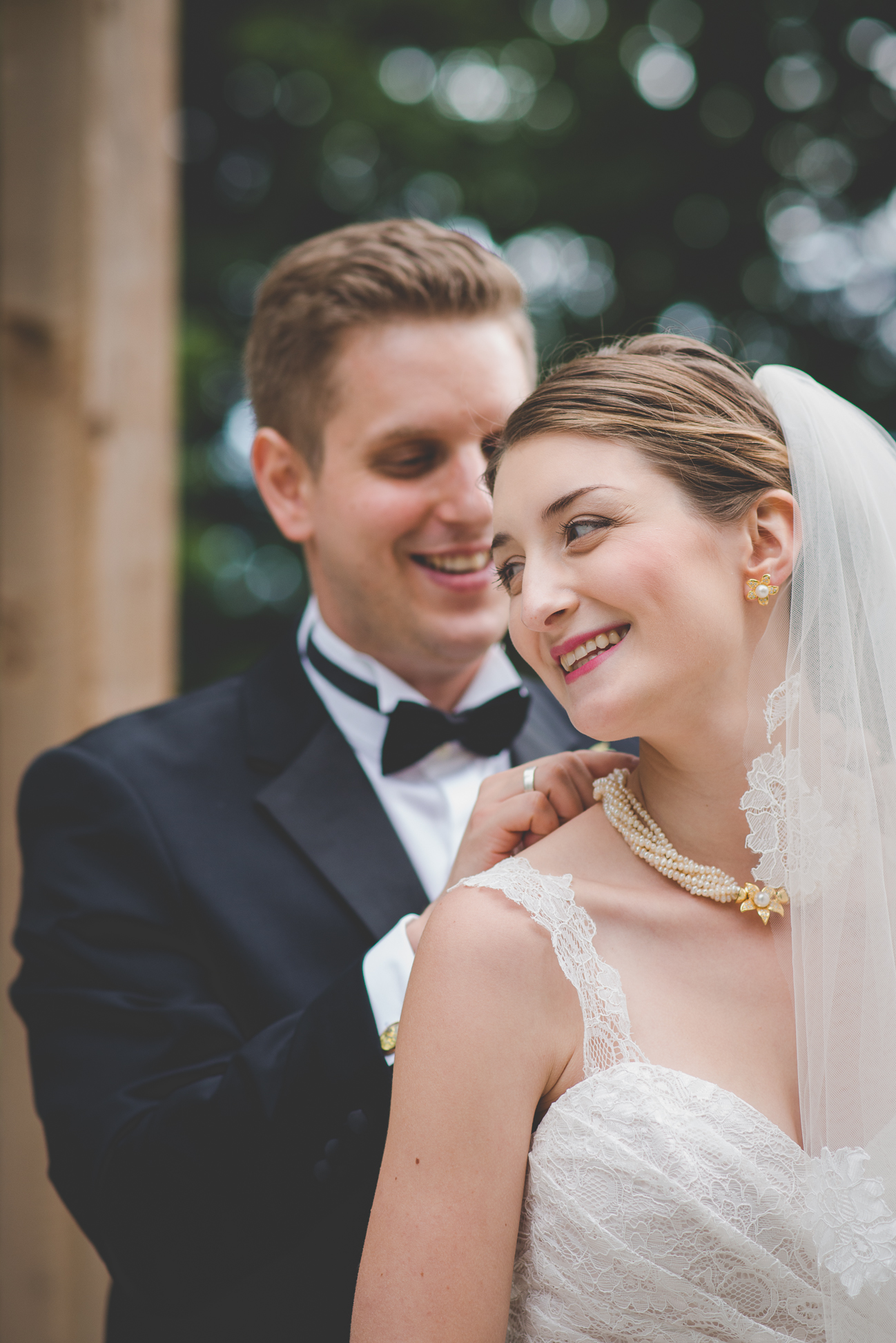 groom helps bride put on pearl necklace designed by mother of the groom