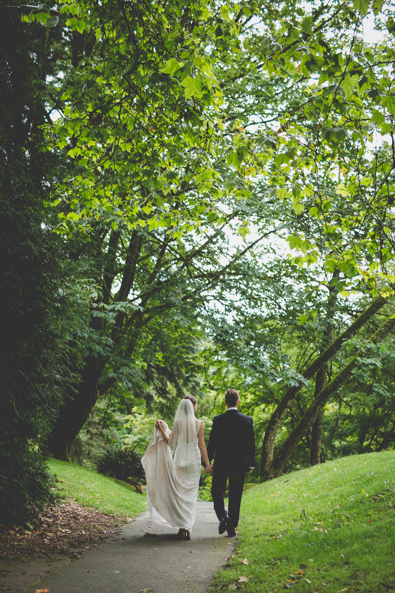 bride and groom holding hands and walking down path while bride carries train of lace wedding dress