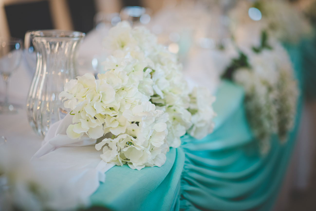 white flowers and turquoise drapery reception decor