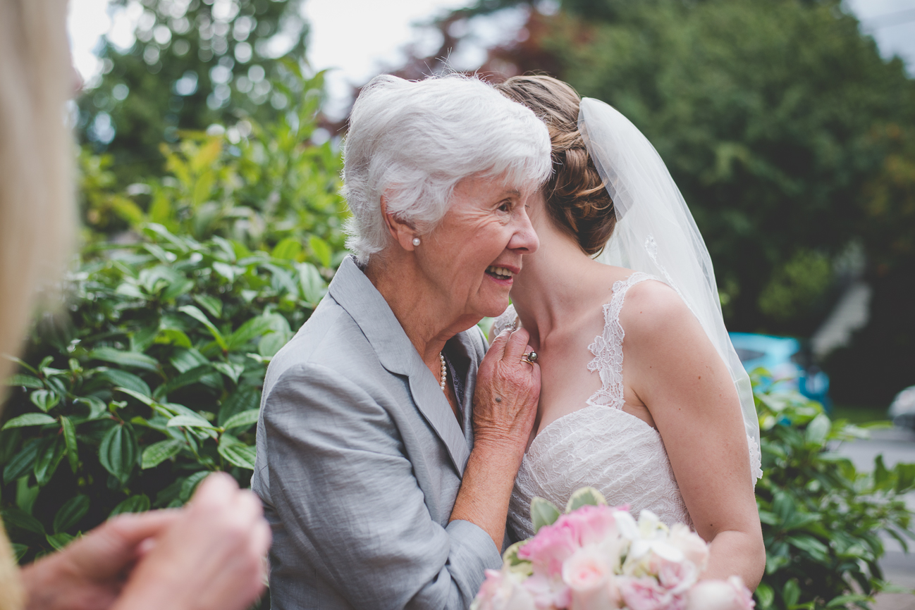 bride in veil and lace wedding dress hugging her grandmother at wedding reception