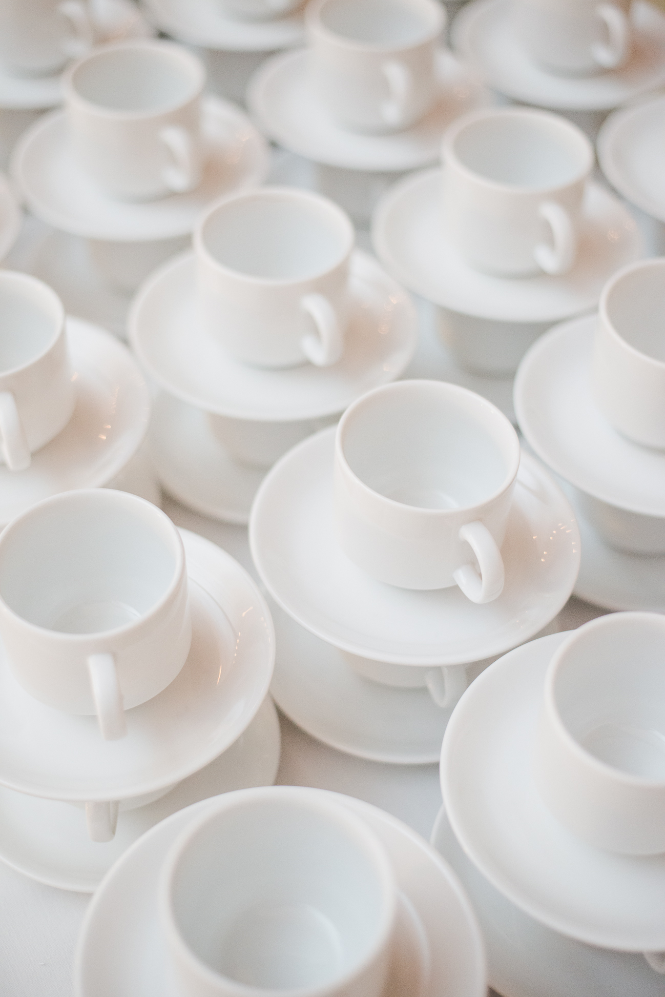stacks of coffee mugs and saucers at wedding reception