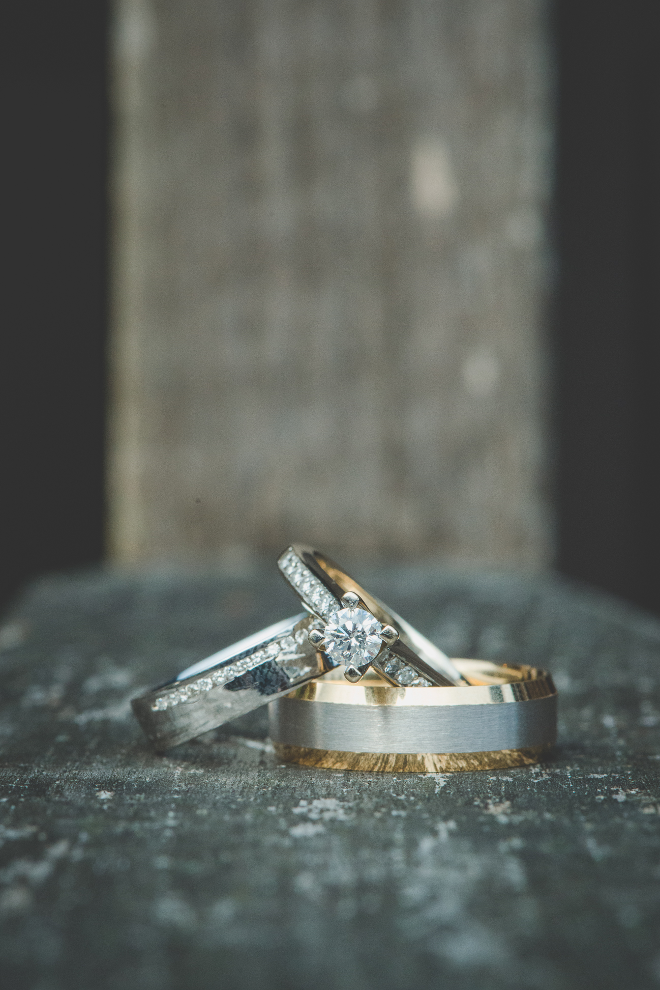bride's wedding ring and engagement ring with groom's wedding band
