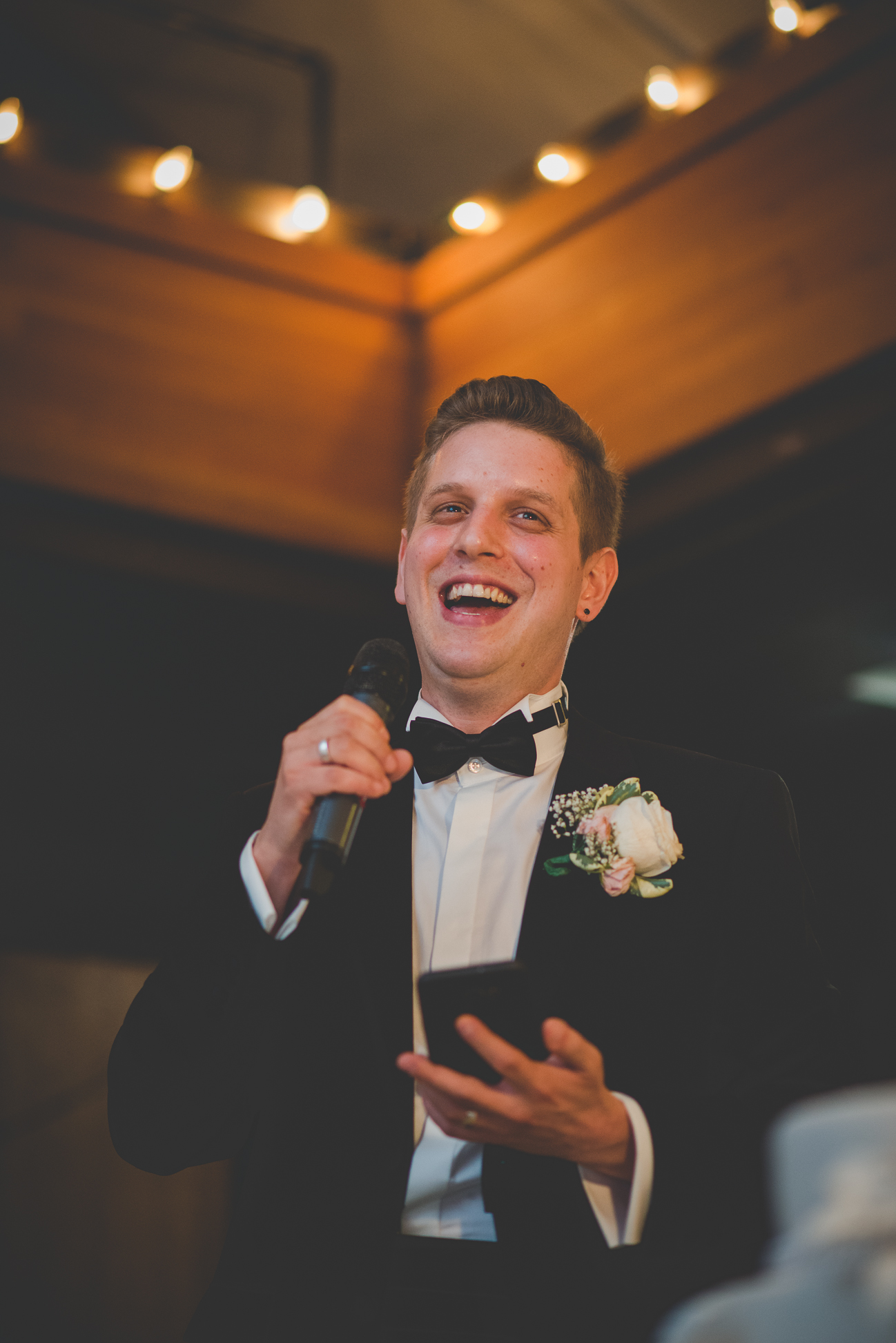 groom giving thank you speech and laughing at wedding reception