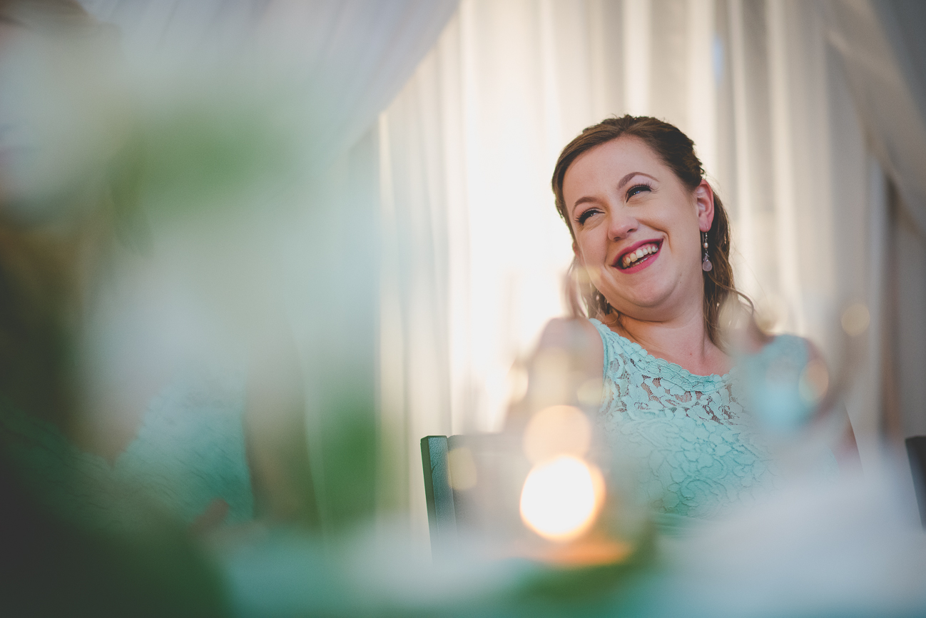maid of honour in turquoise lace dress laughing during speeches at wedding reception