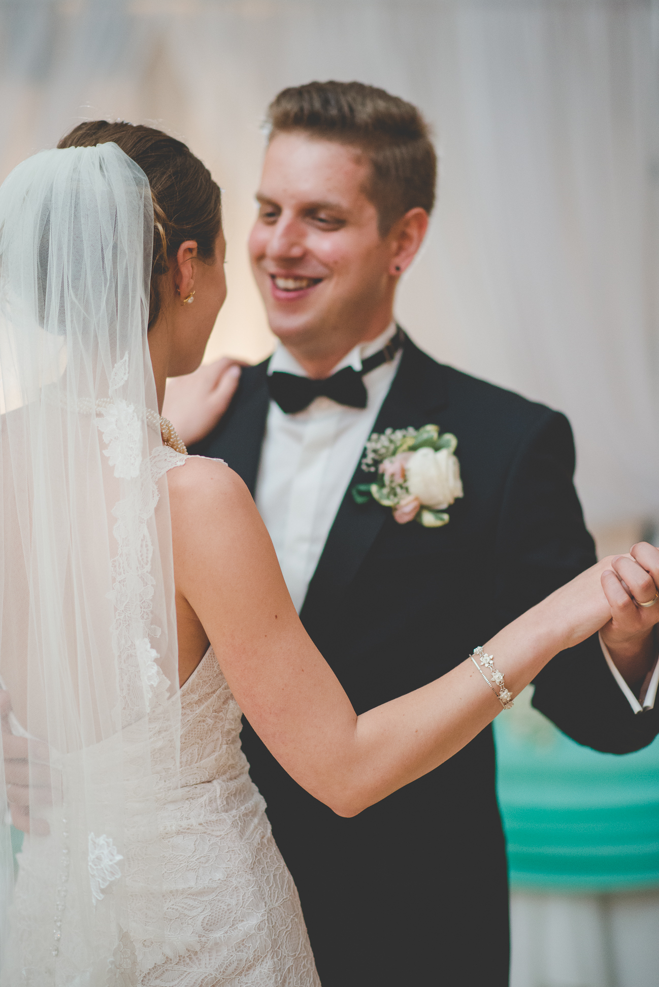 groom smiles at bride in lace wedding dress and veil during first dance as husband and wife
