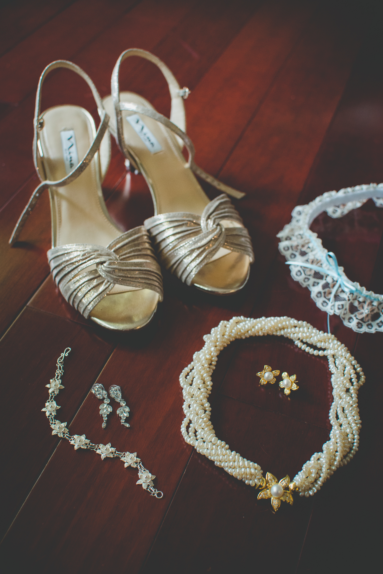 bride's golden wedding shoes, silver flower bracelet and filigree earrings, pearl necklace with golden flower and matching golden flower earrings, and white lace garter with blue ribbon