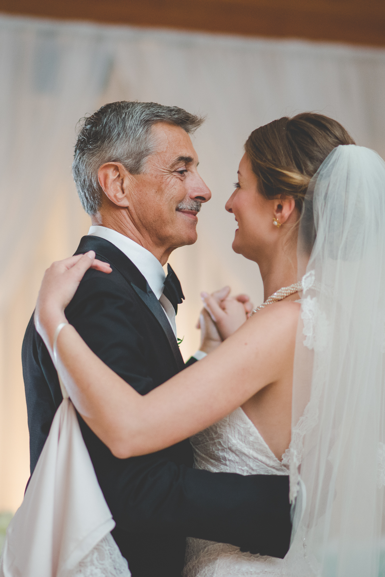 father of the bride smiles at his daughter during father daughter dance at wedding reception