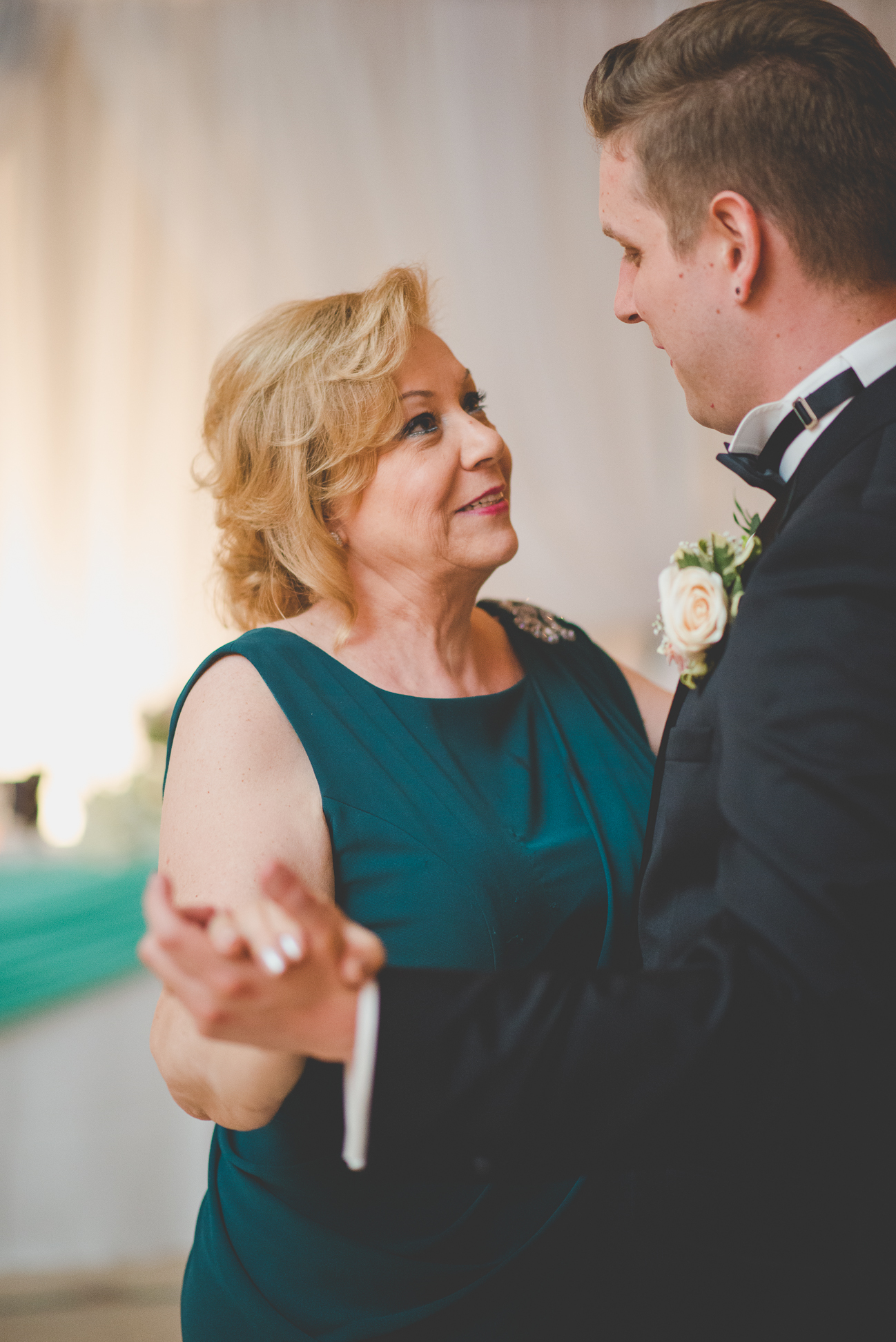 mother of the groom smiles at her son during mother son dance at wedding reception