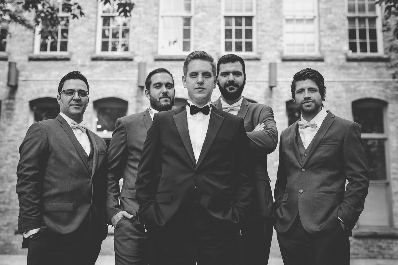 groom and groomsmen wearing bow ties in front of brick building in Yaletown